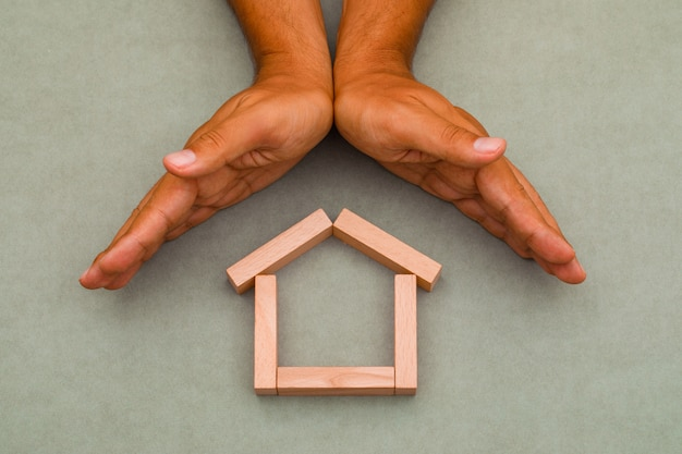 Hands enclosing wooden house. Free Photo