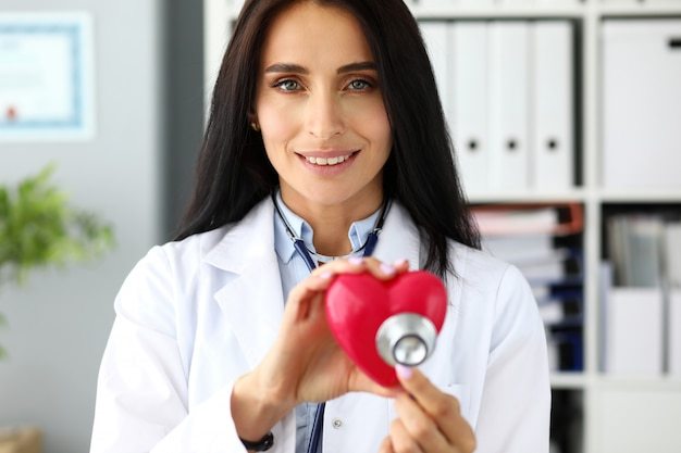 Hands of female gp holding stethoscope head near red toy heart as cardiac problems prophylaxis and recovery symbol portrait Premium Photo