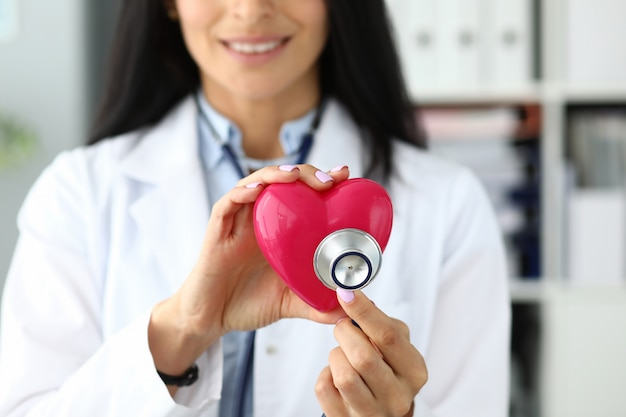 Hands of female gp holding stethoscope head near red toy heart Premium Photo