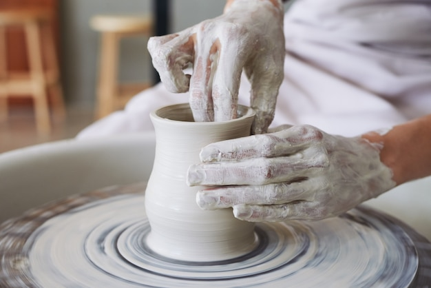 Hands of female potter making clay vase on spinning wheel in workshop Free Photo