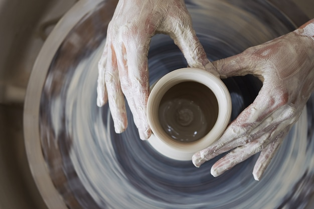 Hands of female potter sculpting clay vessel on spinning wheel Free Photo