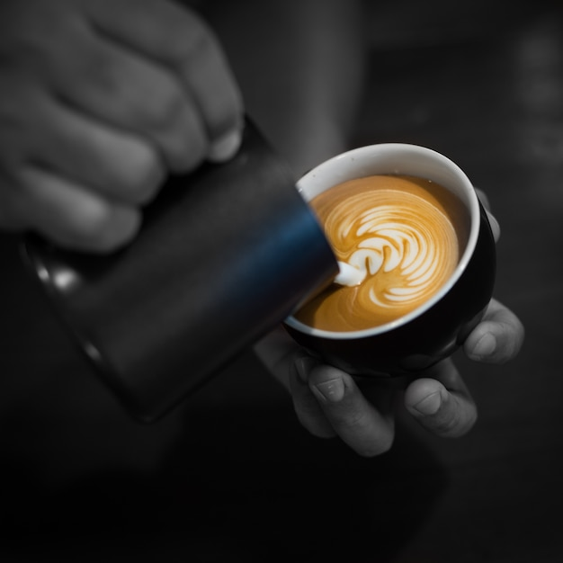 Hands filling a cup of coffee with milk Free Photo