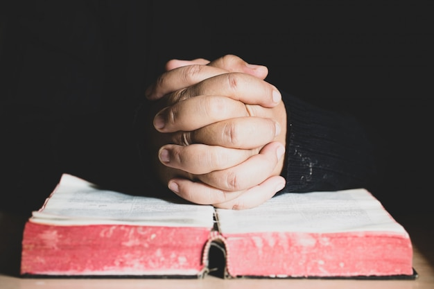 Hands folded in prayer on a holy bible in church concept for faith, spirtuality and religion Premium Photo