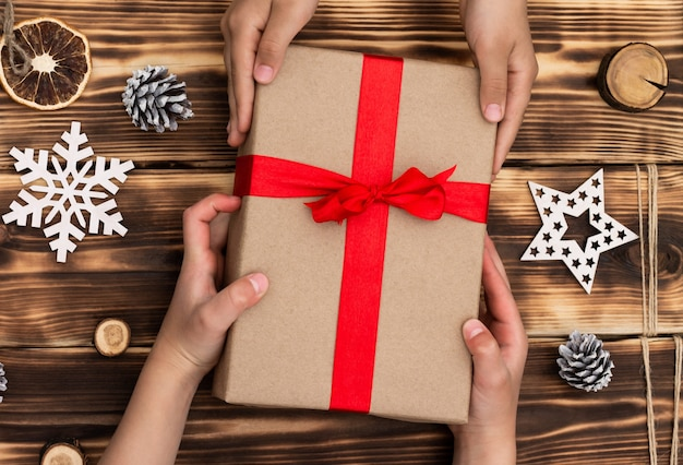 Hands giving or receiving a gift in craft paper with a red ribbon on rustic wood christmas and new year background. top view Premium Photo
