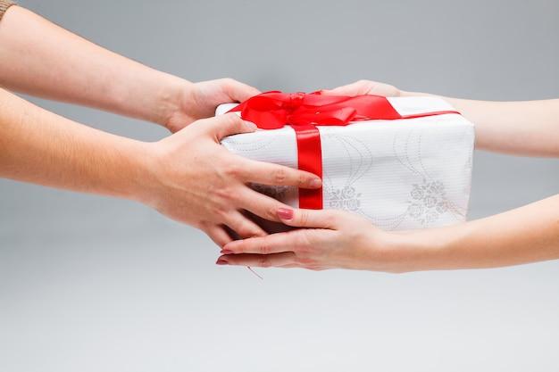 Le mani che danno e ricevono un regalo su sfondo bianco Foto Gratuite