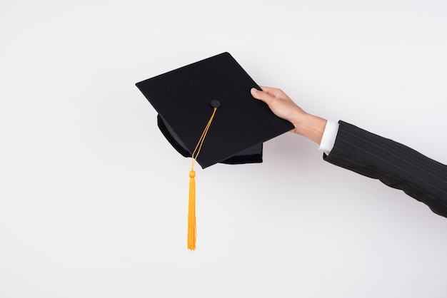 The hands of graduates holding a hat to throw a hat on isolated background. Premium Photo