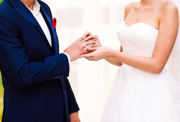 Hands of the groom and bride is wearing a ring on the finger on the day Premium Photo
