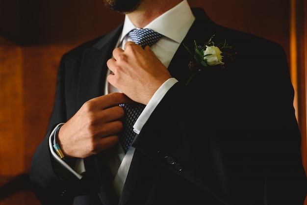 Hands of groom knotting his tie to the bridal fashion before going to the ceremony. Premium Photo