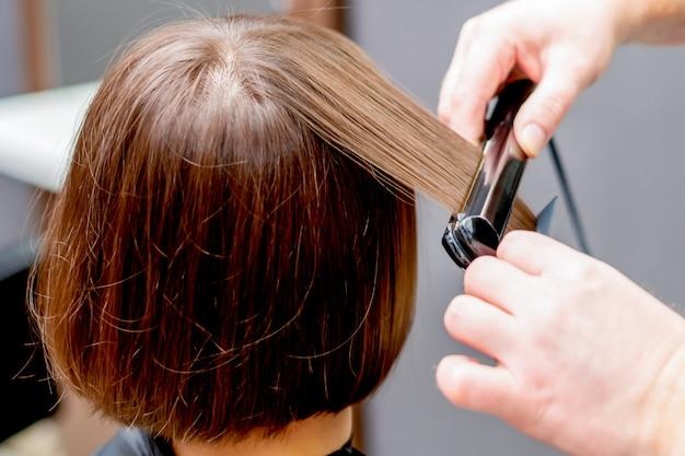 Premium Photo Hands Of Hairdresser Straightening Hair Of Woman