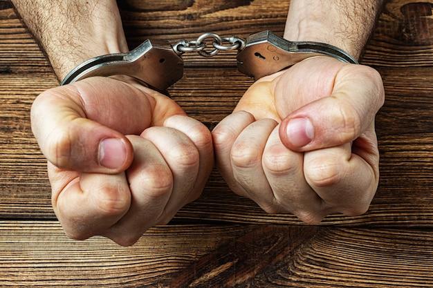 Hands in handcuffs on the dark wooden Premium Photo
