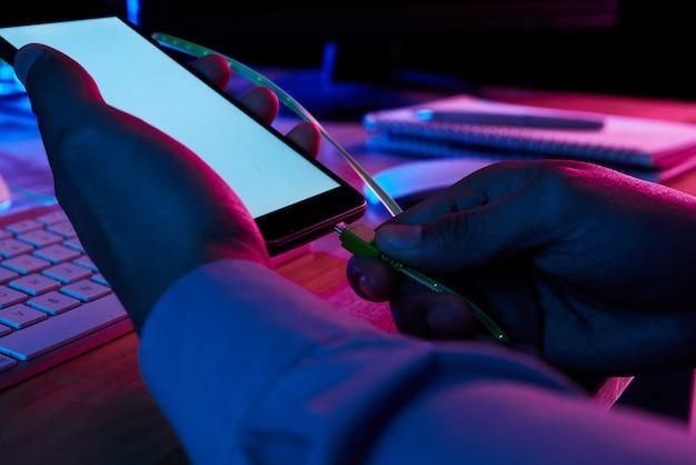 Mani delle mani che mettono il mini canble usb nel connettore dello smartphone Foto Gratuite