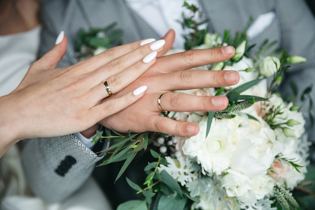 Hands of a handsome husband and wife on the day of their wedding Free Photo