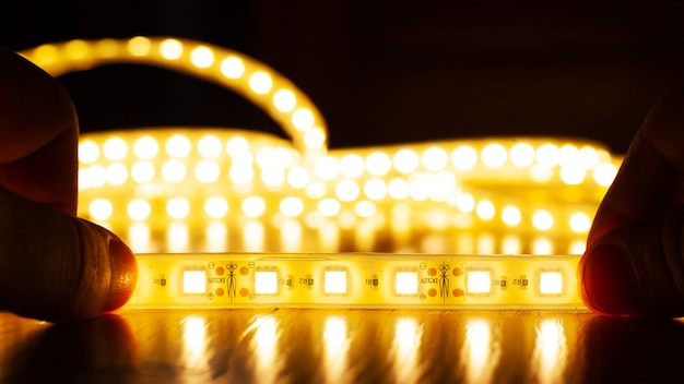 Hands hold a led strip of a warm spectrum Premium Photo
