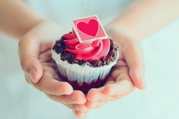 手はバレンタインカップケーキを保持します。 Premium写真