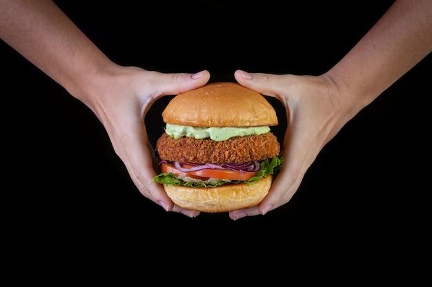 レタス、トマト、紫タマネギ、手作りマヨネーズのチキンバーガーを黒の背景に持つ手。おいしい。 Premium写真