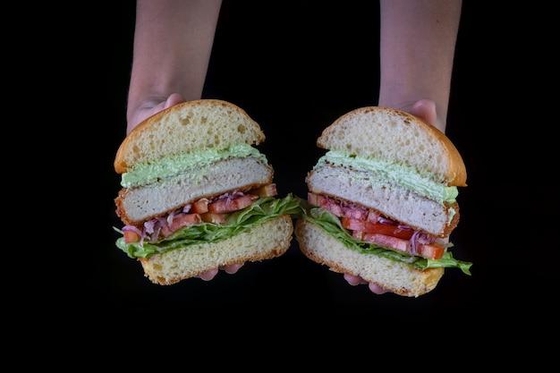 Руки держат куриный бургер с листьями салата, помидор, пурпурный лук и майонез ручной работы на черном backgorund. очень вкусно. Premium Фотографии