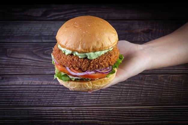 Руки держат куриный бургер с листьями салата, помидор, пурпурный лук и ручной майонез на деревянный фон. очень вкусно. Premium Фотографии
