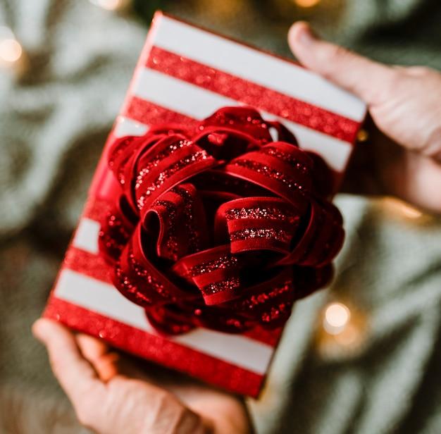 Руки, держащие рождественский тематический подарок Бесплатные Фотографии