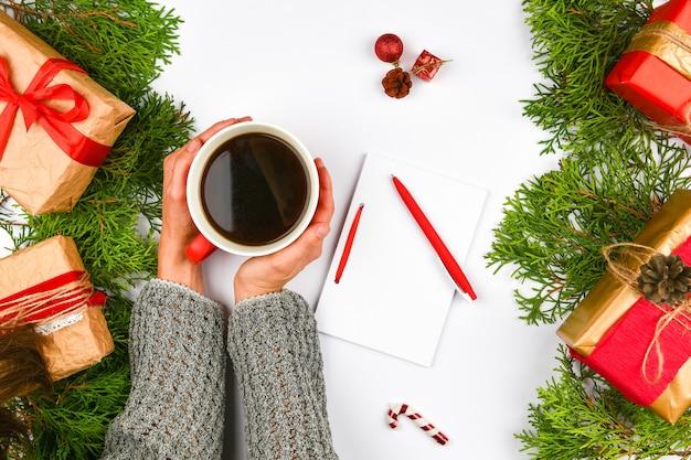 Руки, держа кружку кофе на рождественском пространстве. вид сверху. женские руки, держа чашку кофе. рождественские подарочные коробки и снежная ель над деревянным столом. вид сверху с копией пространства. Premium Фотографии