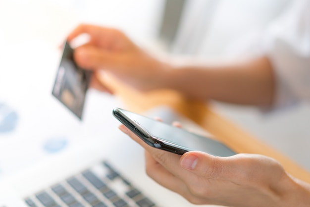 Hands holding a credit card using laptop computer and mobile phone for online shopping Free Photo