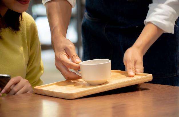 カフェで顧客のためにコーヒーを持っている手。 Premium写真