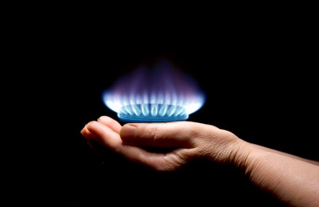 Руки, держащие пламя газа Premium Фотографии