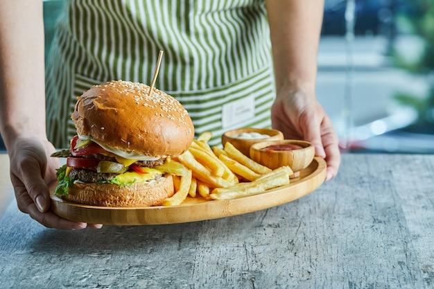 ハンバーガーとフライドポテトとケチャップとマヨネーズの木製プレートを持っている手。 無料写真