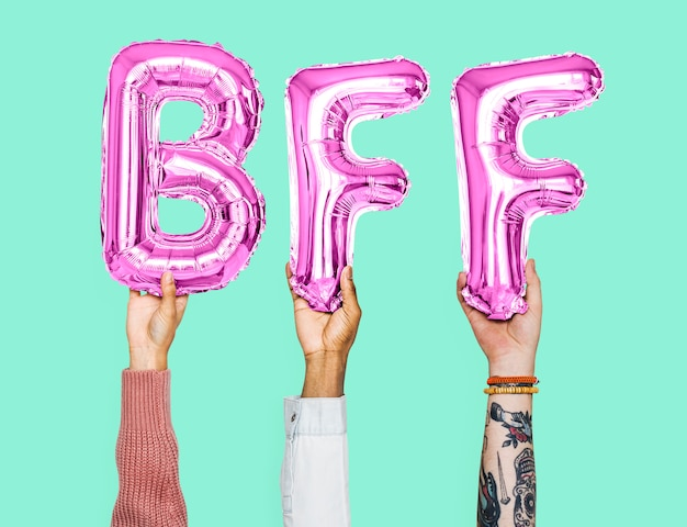 Hands holding bff word in balloon letters Premium Photo
