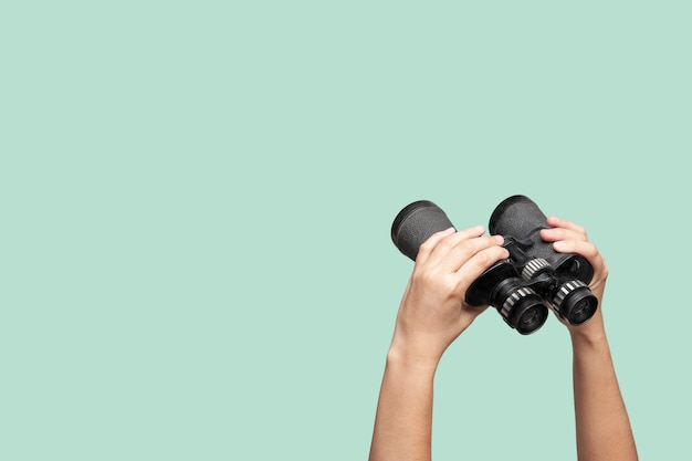 Hands holding binoculars on green background Premium Photo