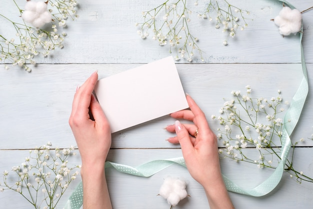 Hands holding blank paper card on light blue wooden desk with flowers. Premium Photo