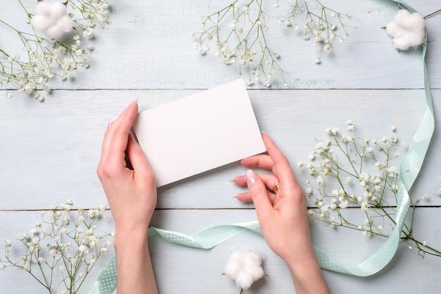 Руки держат чистый лист бумаги на светло синий деревянный стол с цветами. Premium Фотографии
