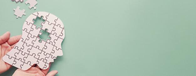 Руки держат мозг с вырезом из бумаги-головоломки, аутизм, осведомленность об эпилепсии и болезни альцгеймера, концепция всемирного дня психического здоровья Premium Фотографии