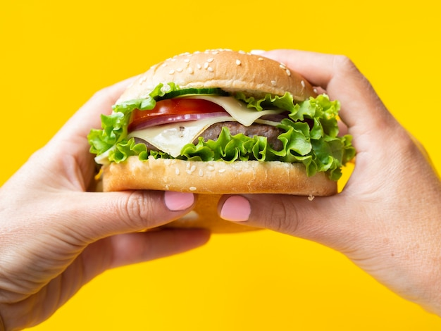 Hands holding a burger on yellow background Free Photo