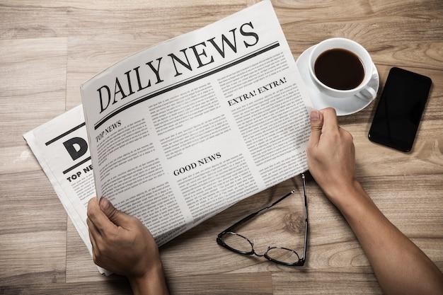 Tangan memegang koran bisnis di atas meja kayu, konsep mock-up koran harian Foto Premium