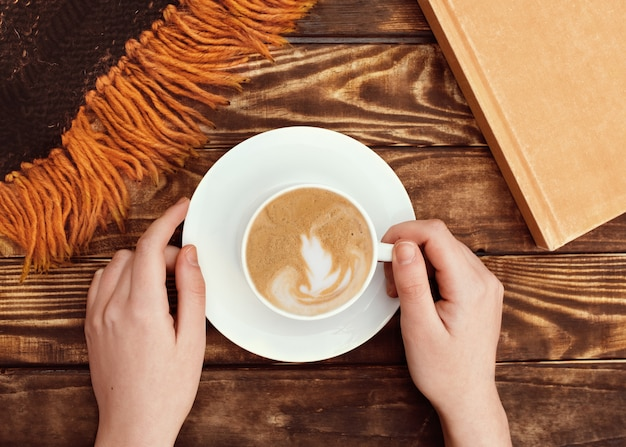 Руки держат крышку с кофе на тарелке, книгу и шерстяной шарф на деревянном фоне Premium Фотографии