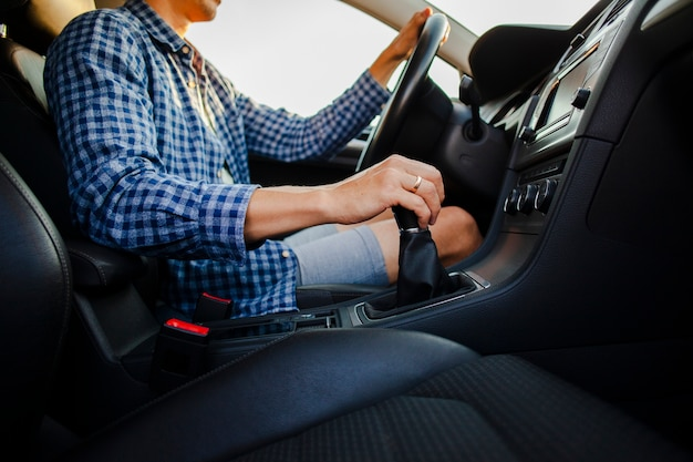 Hands holding car wheel and gear stick Free Photo