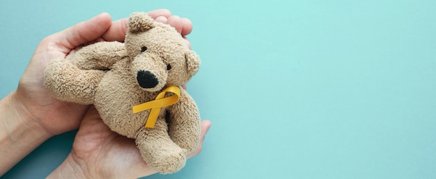 Hands holding children soft toy brown bear with yellow gold ribbon Premium Photo