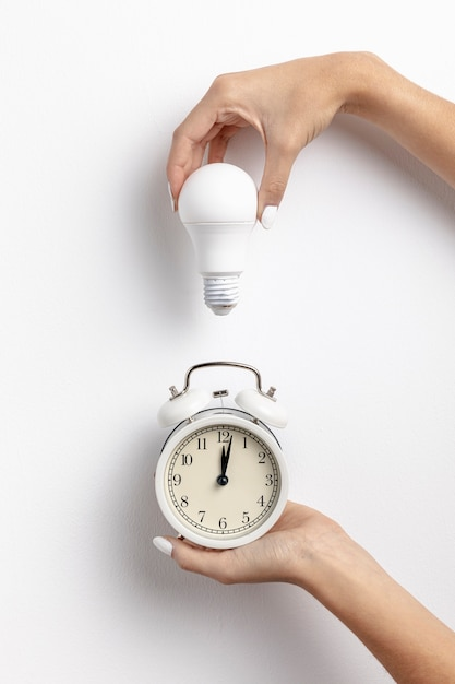 Руки держат часы и лампочку Бесплатные Фотографии