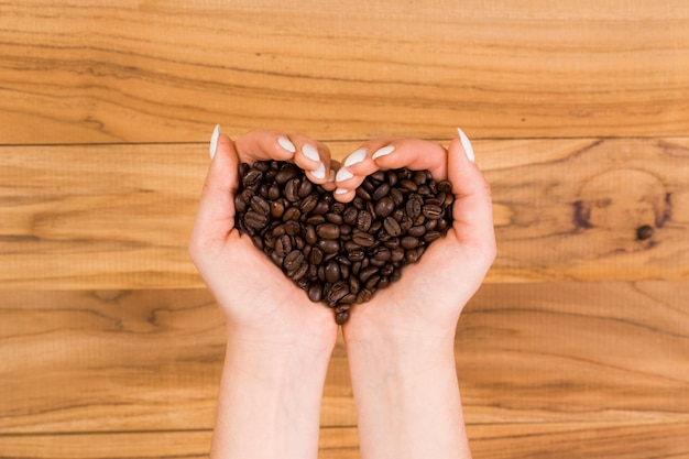 Hands holding coffee beans Free Photo
