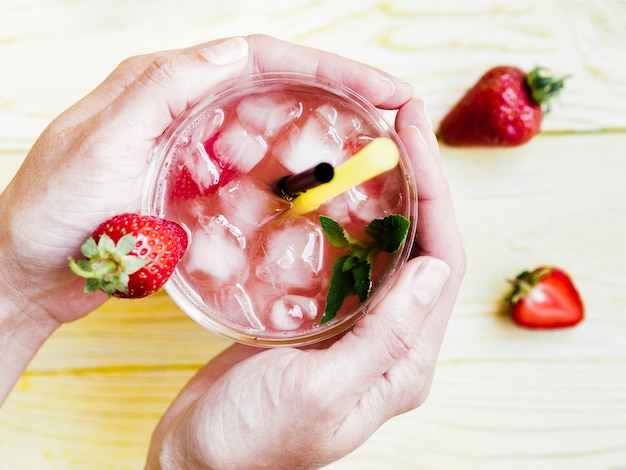 Hands holding cold cup of strawberry drink Free Photo