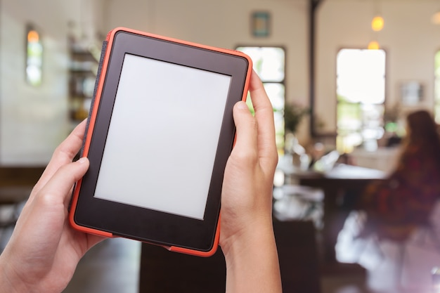 Hands holding computer tablet with coffee shop background Premium Photo