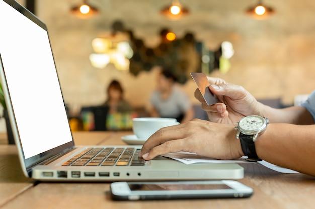 Руки держа кредитную карточку и используя компьтер-книжку клавиатуры на таблице. Premium Фотографии