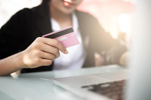 Руки держат кредитную карту и используя ноутбук. Premium Фотографии