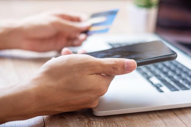 Hands holding credit card and smartphone | Premium Photo