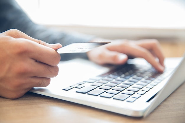 Hands holding credit card and typing on laptop Free Photo