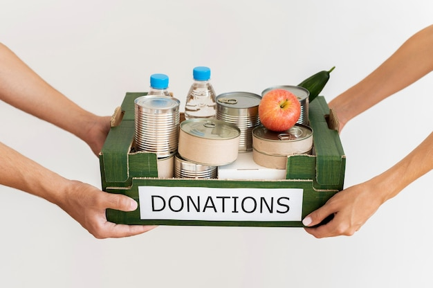Hands holding donation box with provisions Free Photo