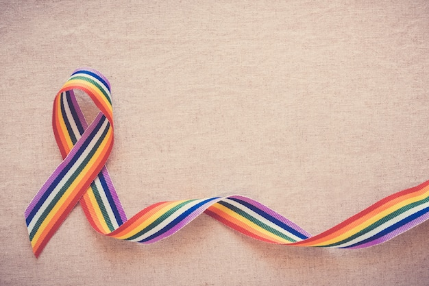 Hands holding gay pride rainbow ribbon for lgbt awareness Premium Photo