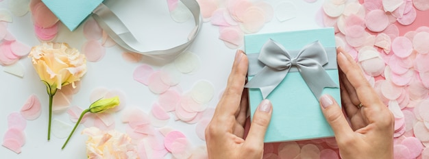 Hands holding gift box banner background Premium Photo