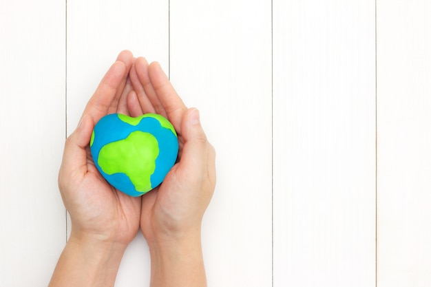 Hands holding global heart shape over white wooden background with copy space. Premium Photo