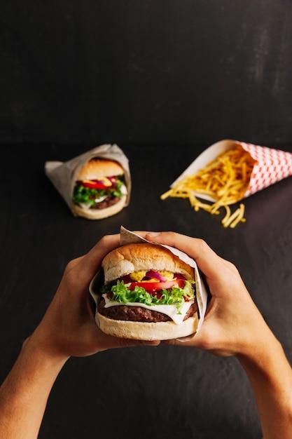 Hands holding hamburger Free Photo